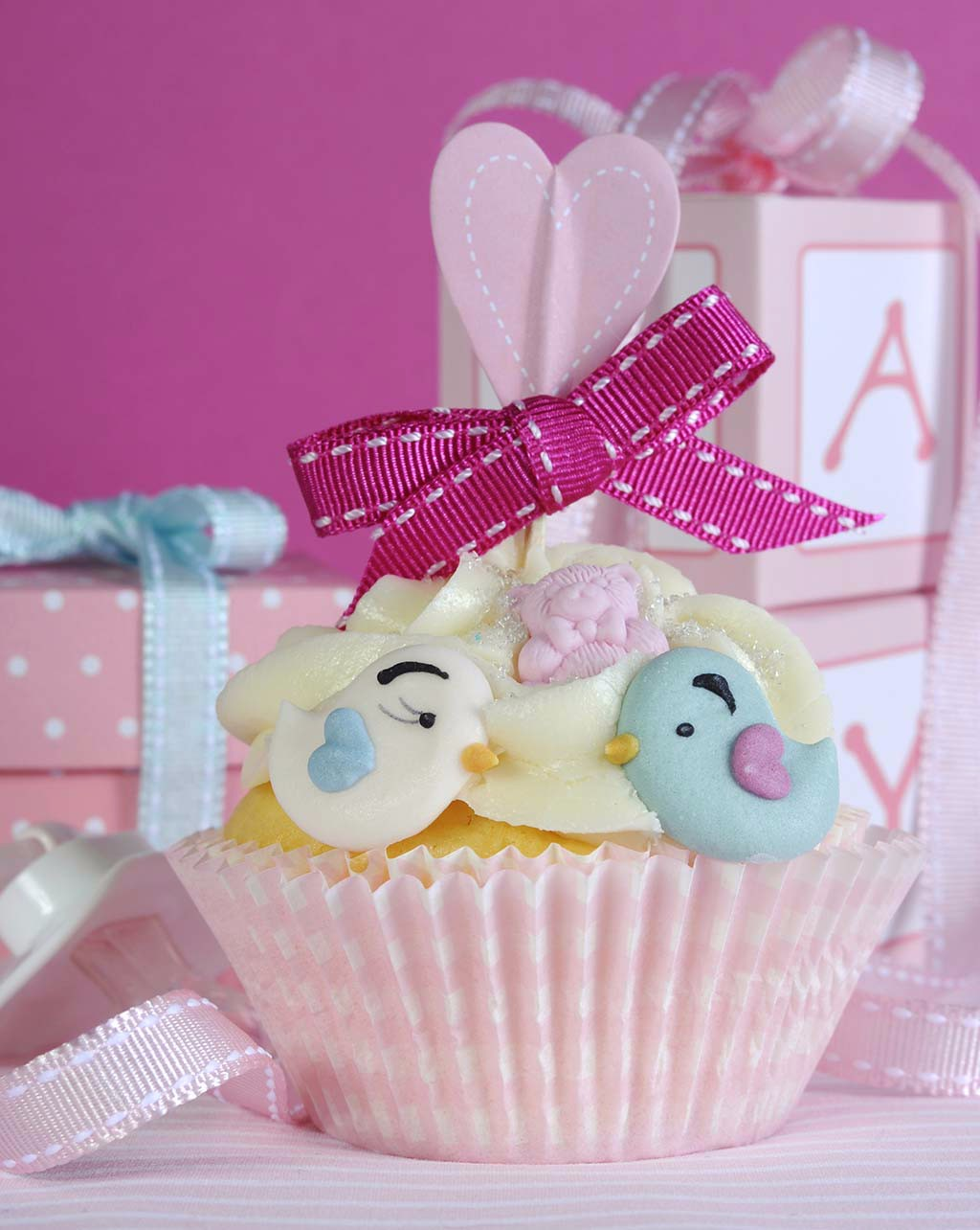 Baby girl cupcake with cute birds and ribbon closeup