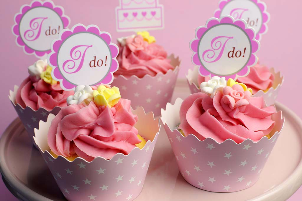 Pink wedding cupcakes with I Do topper signs on pink cake stand