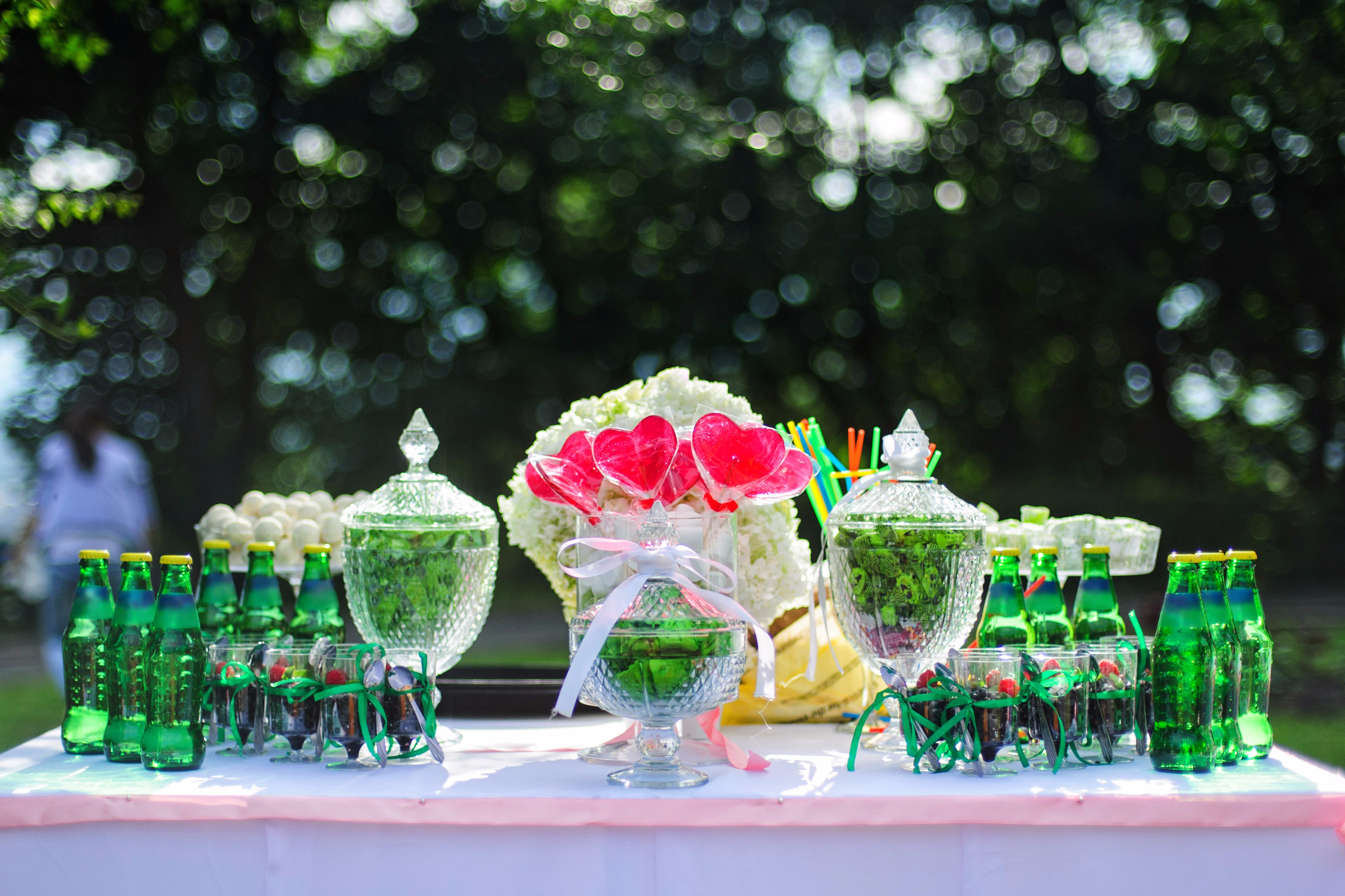 Green wedding candy bar with red hearts and bottles for drinks